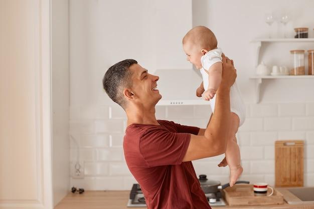 Zijaanzichtportret van een gelukkige knappe vader die een bordeauxrood t-shirt draagt met een charmante dochter, een opgevoed meisje, die geluk en positieve emoties uitdrukt.