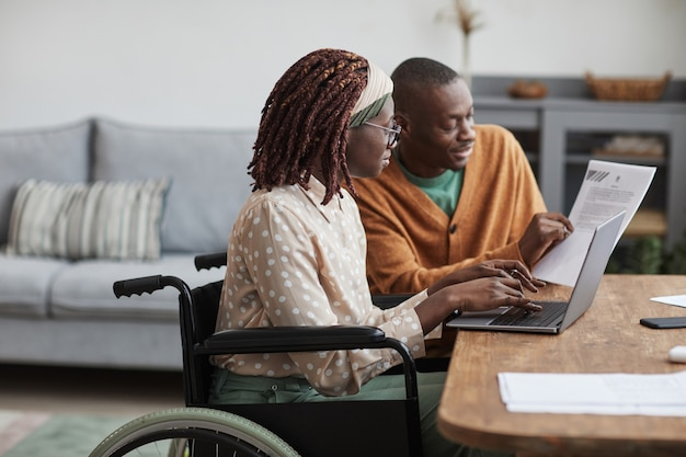 Zijaanzichtportret van een jonge afro-amerikaanse vrouw die een rolstoel gebruikt die vanuit huis werkt, terwijl haar echtgenoot haar helpt de ruimte te kopiëren