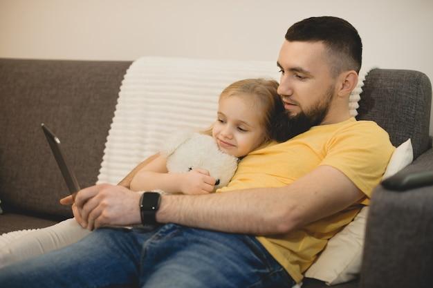 Zijaanzichtportret van een jonge bebaarde vader die met zijn dochter naar een tablet kijkt terwijl hij thuis op een bank leunt.
