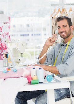 Zijaanzichtportret van een jonge mannelijke manierontwerper die telefoon in de studio met behulp van