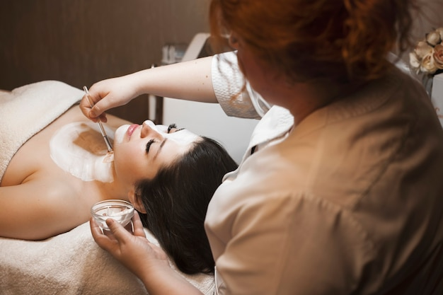 Zijaanzichtportret van een jonge mooie brunette met een wit huidverzorgingsmasker door een vrouwelijke schoonheidsspecialist in een wellness-spa salon.