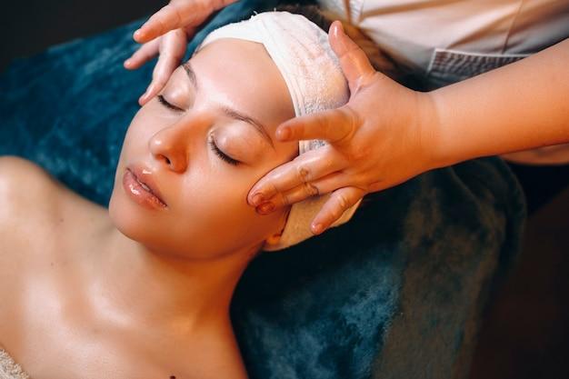 Zijaanzichtportret van een jonge vrouw die een huidverzorgingsroutine hebben in een kuuroordcentrum.