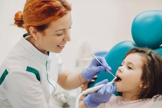 Zijaanzichtportret van een jonge vrouwelijke pediatrische stomatologist die tandenoperatie doet aan een klein leuk meisje.