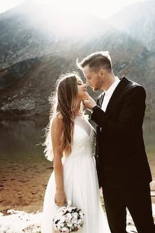 Zijaanzichtportret van een leuk jong kaukasisch paar die aan elkaar glimlachen alvorens tegen meer en berg in de ochtend te kussen.