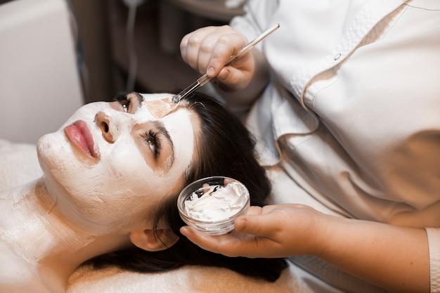 Zijaanzichtportret van een leuke jonge vrouw die in wellness-spa ontspant terwijl het hebben van een wit masker op het gezicht.