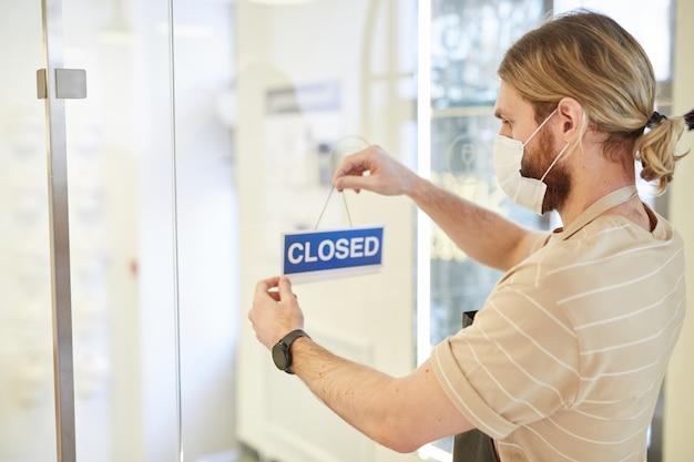 Zijaanzichtportret van een man die een gesloten bord op de glazen deur in het café hangt en een masker draagt, covid-beperkingen, kopieerruimte