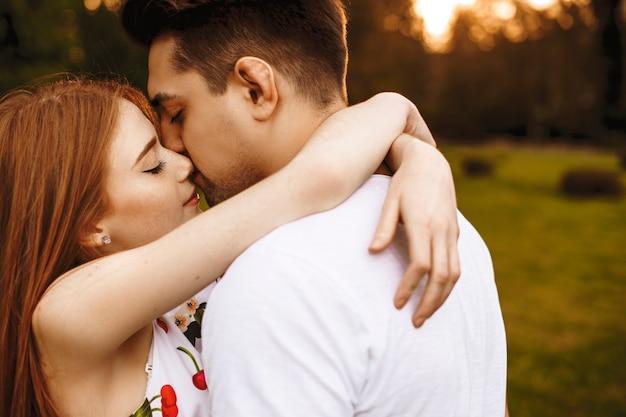 Zijaanzichtportret van een mooi jong kaukasisch paar dat en buiten omhelst kussen terwijl dat tegen zonsondergang dateert.