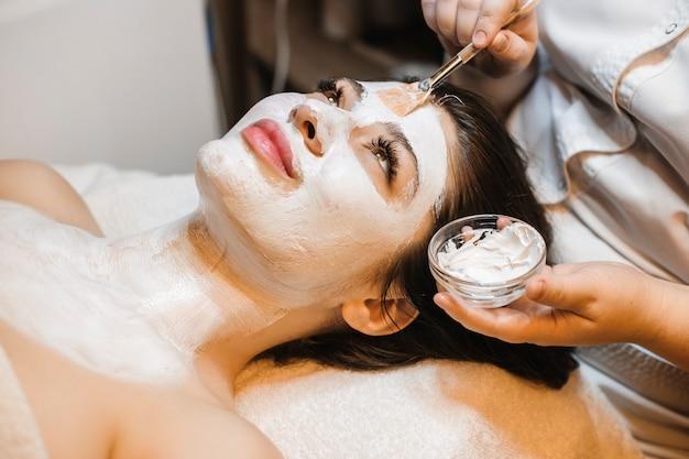 Zijaanzichtportret van een mooie jonge bedrijfsvrouw die in een wellnesscentrum ontspannen na het werk die lichaams- en gezichtsprocedures doet.