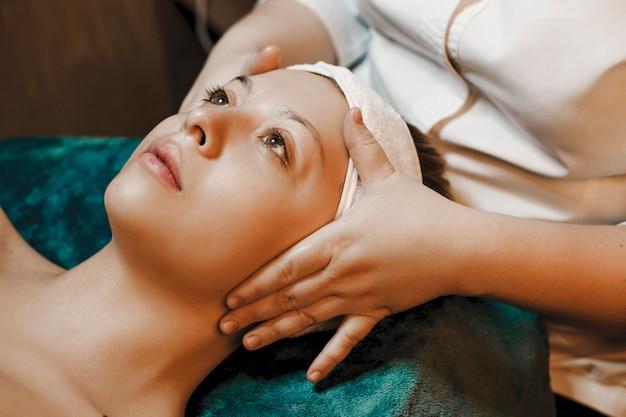 Zijaanzichtportret van een mooie jonge vrouw die een gezichtsmassage hebben vóór gezichtstherapie terwijl leunend op een kuuroordbed opzoeken.