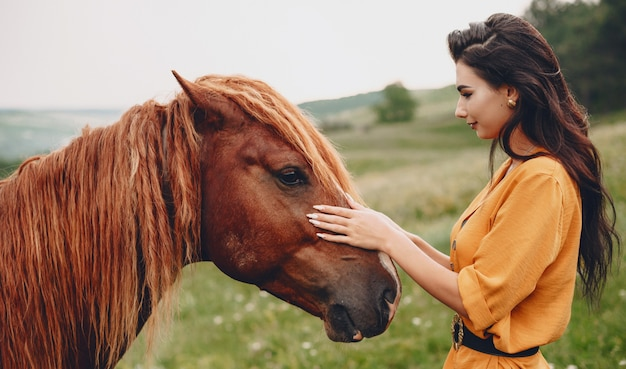 Zijaanzichtportret van een mooie jonge vrouw die een paard in de bergen aanraakt tijdens het reizen.