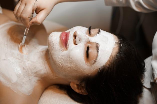 Zijaanzichtportret van een mooie vrouw die op een bed met gesloten ogen leunt die een wit masker op het gezicht en de hals doen.