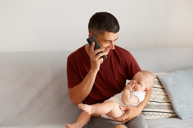Zijaanzichtportret van een positieve donkerharige vader die via de mobiele telefoon praat en een dochtertje in zijn handen houdt, een prettig gesprek voert, tijd doorbrengt met zijn kind.