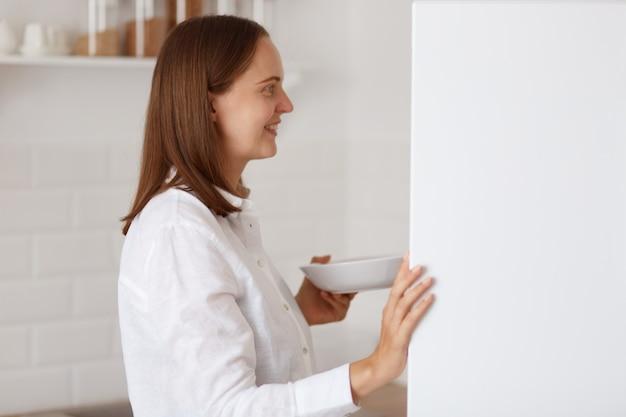 Zijaanzichtportret van een positieve donkerharige vrouw met een wit overhemd, het openen van de koelkast, het vinden van voedsel voor ontbijt of diner, glimlachend in de koelkast.