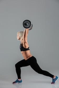 Zijaanzichtportret van een sterke spier volwassen sportvrouw