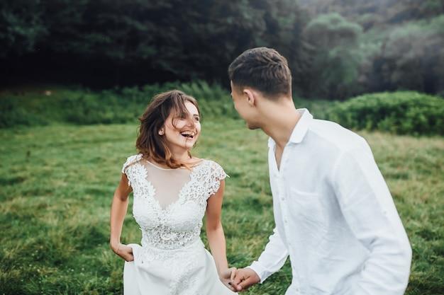 Zijaanzichtportret van een verbazend echtpaar die elkaar aankijken en handen glimlachen