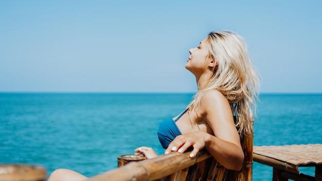Zijaanzichtportret van een vrouw die ontspant en frisse lucht inademt op het strand