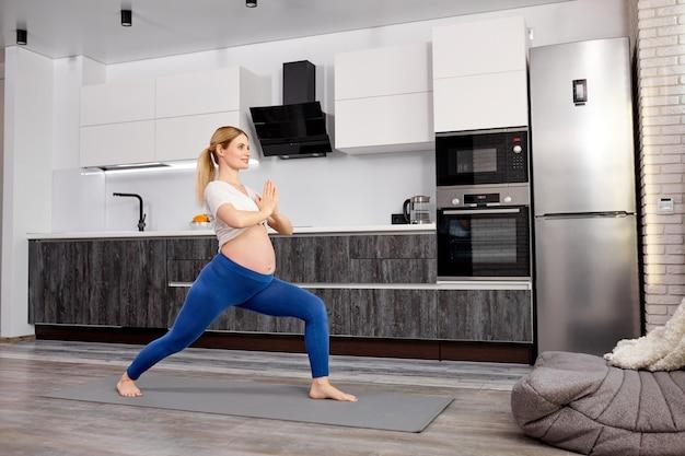 Zijaanzichtportret van een vrouw die yoga-oefeningen doet die met de benen uit elkaar staan en de handen bij elkaar houden en kalm blijven