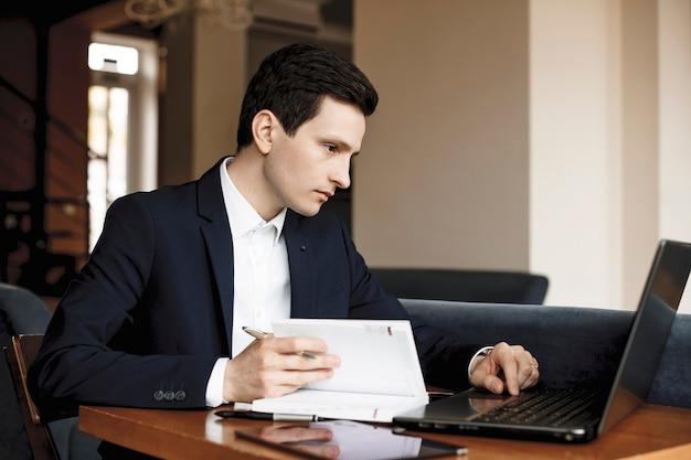 Zijaanzichtportret van een zelfverzekerde serieus jonge manager die in een modern kantoor werkt dat in een notitieboekje schrijft en naar een laptop kijkt.