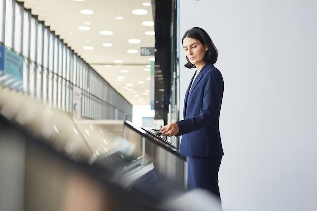 Zijaanzichtportret van eigentijdse zakenvrouw uit het midden-oosten die telefoon veegt tijdens het passeren van tourniquet poort in luchthaven of kantoorgebouw,