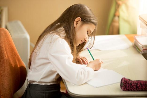 Zijaanzichtportret van geconcentreerd schoolmeisje dat bij oefenboek schrijft