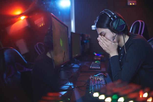 Zijaanzichtportret van gefrustreerde aziatische man die gezicht bedekt na het verliezen van videogameconcurrentie, exemplaarruimte