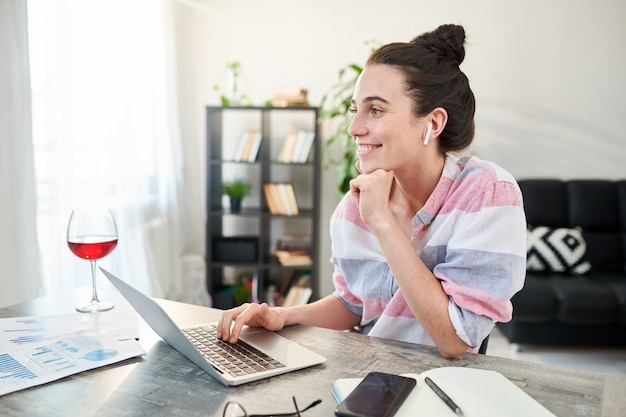 Zijaanzichtportret van het eigentijdse jonge vrouw gelukkig glimlachen terwijl het werken van huis, exemplaarruimte