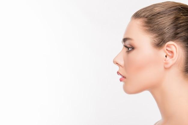Zijaanzichtportret van het gezicht van de aantrekkelijke vrouw op wit