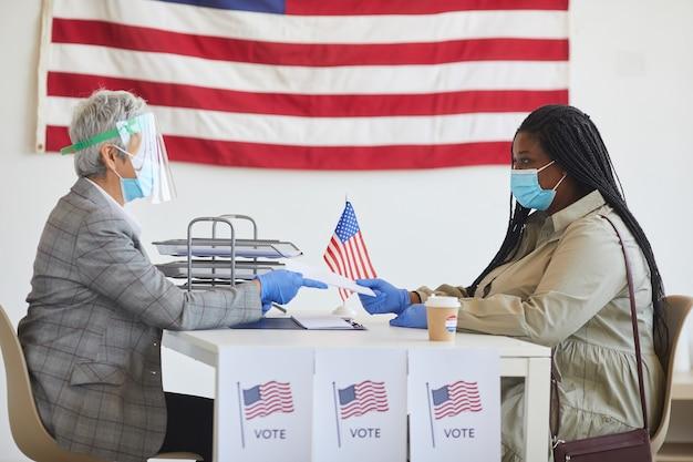 Zijaanzichtportret van jonge afrikaans-amerikaanse vrouw die masker draagt terwijl ze zich registreert om te stemmen op de verkiezingsdag na de pandemie, kopie ruimte