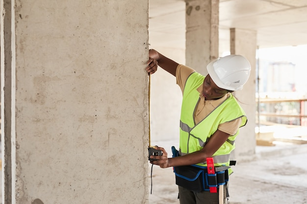 Zijaanzichtportret van jonge afro-amerikaanse vrouw die werkt op de kopieerruimte van de bouwplaats