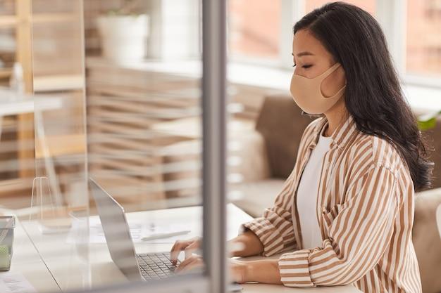 Zijaanzichtportret van jonge aziatische vrouw die masker draagt en laptop gebruikt tijdens het werken bij bureau in bureaucel, exemplaarruimte