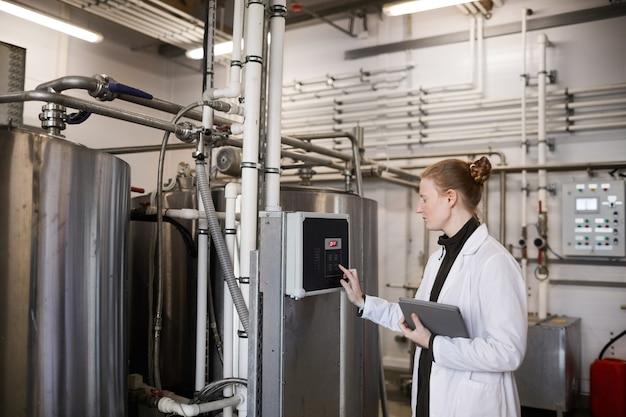 Zijaanzichtportret van jonge werkneemster die machines in werking stelt bij zuivelfabriek, exemplaarruimte
