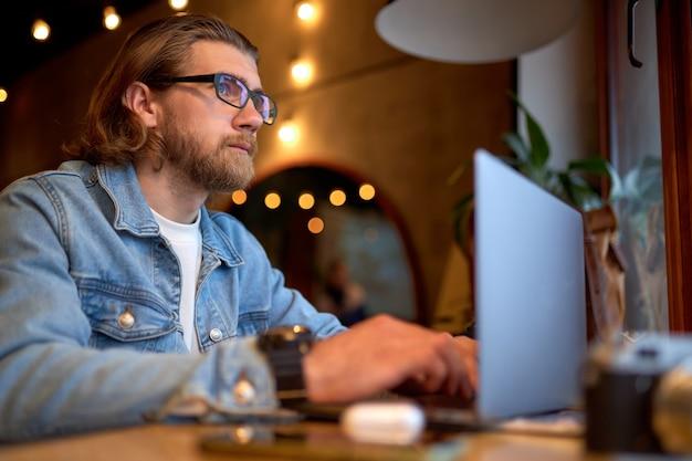 Zijaanzichtportret van knappe blanke kerel in spijkerjasje die op laptop werkt