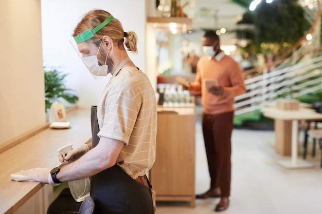 Zijaanzichtportret van mannelijke cafémedewerker die een masker en gezichtsschild draagt terwijl hij tafels schoonmaakt en meubels schoonmaakt, kopieer ruimte