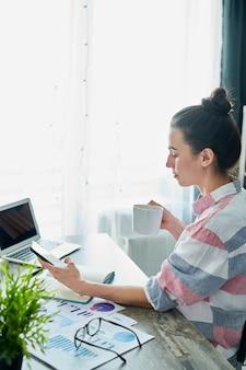 Zijaanzichtportret van moderne jonge vrouw die van koffie genieten terwijl thuis het werken, exemplaarruimte