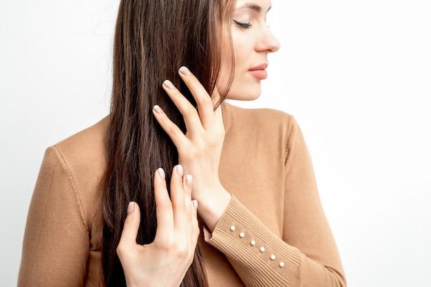 Zijaanzichtportret van mooie jonge kaukasische donkerbruine vrouw met gesloten ogen die haar haar aanraken door gemanicuurde vingers op witte muur