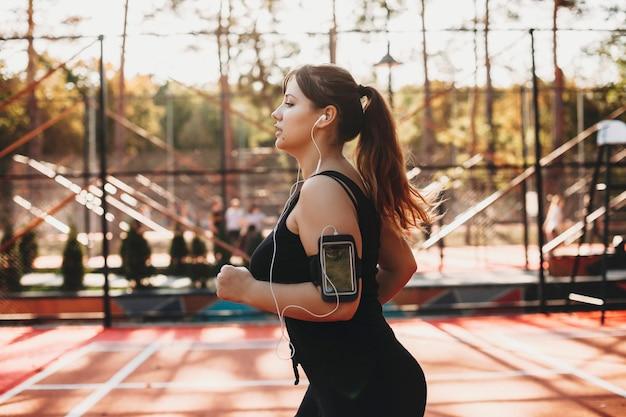 Zijaanzichtportret van mooie plus grootte vrouwen die in de ochtend in een sportpark lopen om af te vallen.