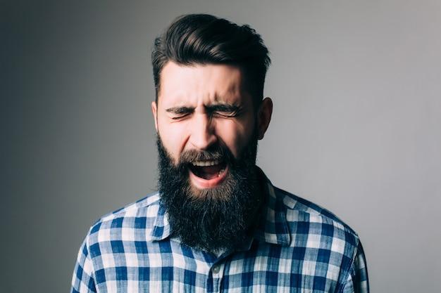 Zijaanzichtportret van schreeuwende bebaarde man - grijze muur