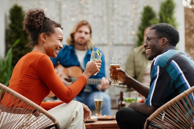 Zijaanzichtportret van twee afro-amerikaanse jongeren die een bril rammelen terwijl ze genieten van een buitenfeest met vrienden op het dak