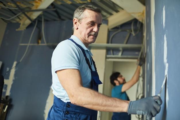 Zijaanzichtportret van twee bouwvakkers die droge muur bouwen tijdens het renoveren van huis, exemplaarruimte