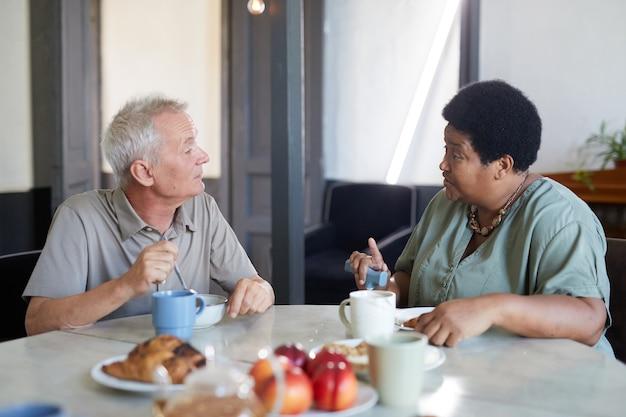 Zijaanzichtportret van twee senioren die genieten van het ontbijt aan tafel in een modern verpleeghuis