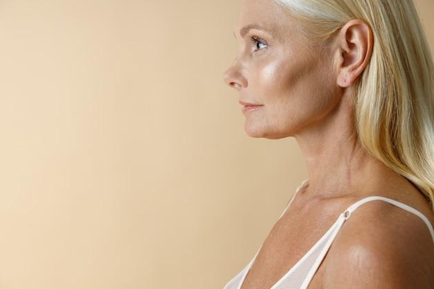 Zijaanzichtportret van vrij rijpe blondevrouw die in wit ondergoed wegkijken terwijl ze geïsoleerd staan
