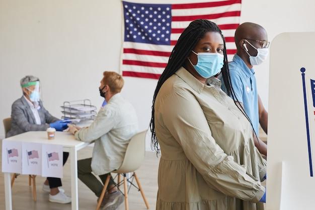 Zijaanzichtportret van vrouwelijke afrikaans-amerikaanse kiezer die zich in cabine en op post-pandemische verkiezingsdag bevindt, exemplaarruimte
