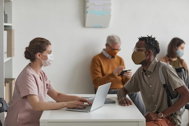 Zijaanzichtportret van vrouwelijke verpleegster die patiënten registreert die in de rij wachten op het kantoor van de dokter, allemaal met maskers, kopieer ruimte