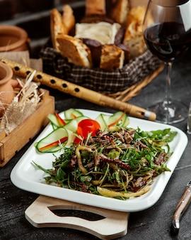 Zijaanzichtsalade met greens en vlees met groenten op een raad met brood