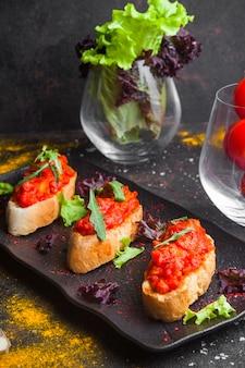 Zijaanzichtsnack met gesneden brood van hierboven tomatensalade en rucola in donkere plaat
