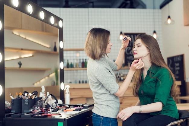 Zijaanzichtstylist met eyeliner die met model werken