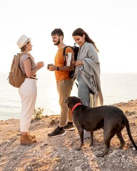 Zijaanzichtvrienden die met een hond reizen