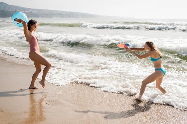 Zijaanzichtvrienden die op strand spelen