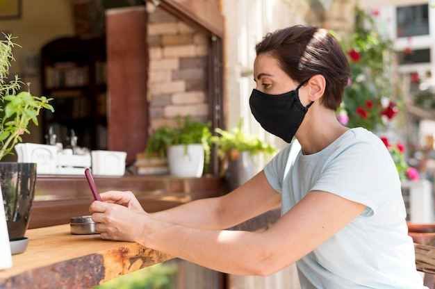 Zijaanzichtvrouw bij terras met masker