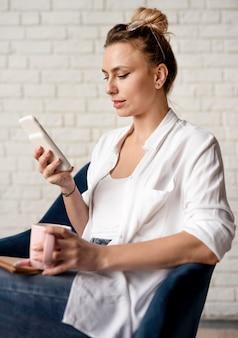 Zijaanzichtvrouw die aan mobiel werken
